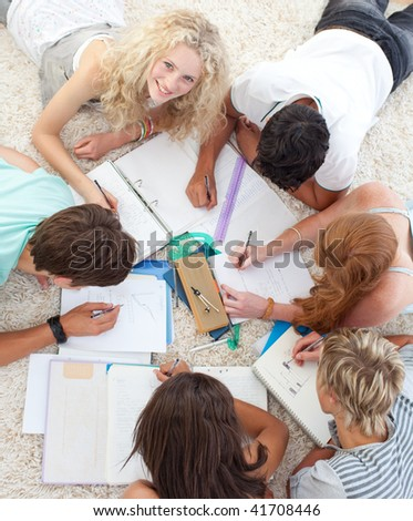 Teens doing homework together on the floor - stock photo