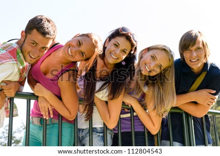 Teens having fun in park leaning fence happy students relaxing - stock photo