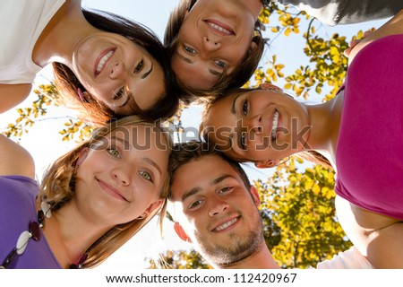 Teens in a circle smiling in park leisure students friends - stock photo