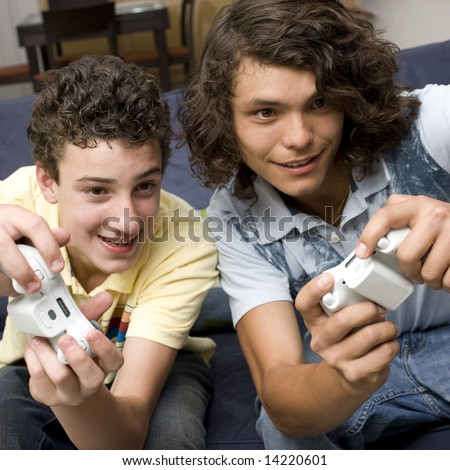 Teens play video games on a couch - stock photo