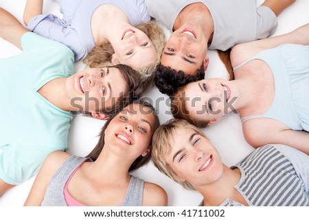 Teens relaxing on floor with heads together in a circle - stock photo
