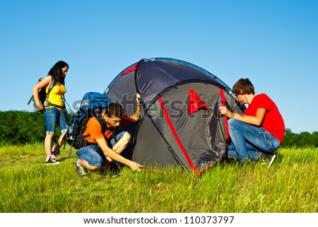 Teens setting a camping tent - stock photo