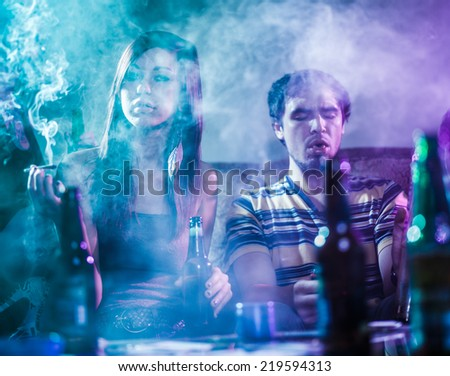 teens smoking marijuana in smoke filled room - stock photo
