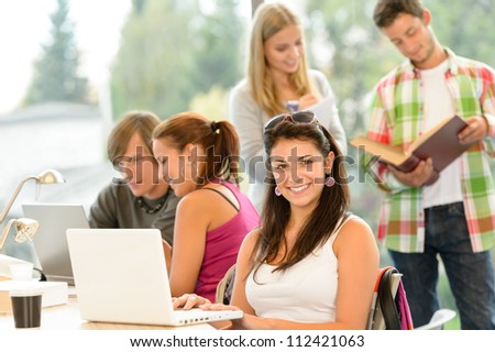 Teens studying in high-school library young pupils smiling laptop book - stock photo