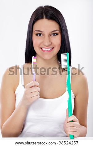 Teeth brushing, funny girl with small and big toothbrush - stock photo