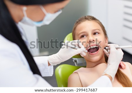 Teeth checkup at dentist's office. Dentist examining girls teeth in the dentists chair - stock photo