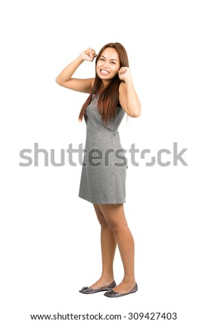 Teeth clenched Asian woman in gray dress with light brown hair, balled fists, looking at camera throwing immature temper tantrum, fed up, annoyed, irritated. Thai national of Chinese origin. - stock photo