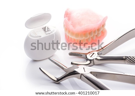 Teeth model with dental floss and forceps on white surface - stock photo