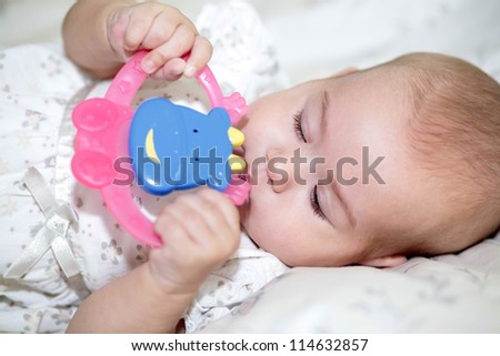 Teething baby playing with teether toy - stock photo