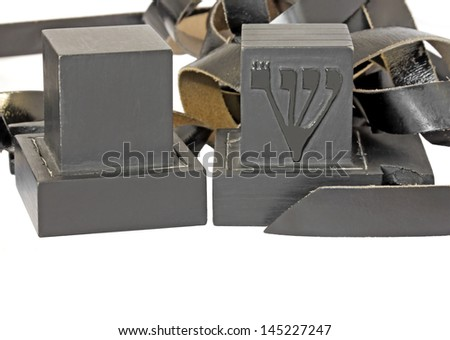 Tefillin isolated on white background.Pair of black boxes,leather straps.Portions of the Torah written on parchment inside.Worn by Jewish men during prayer.Shallow depth of field,blurred background - stock photo