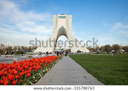 TEHRAN, IRAN - APRIL 1, 2014: Azadi Square decorated with grass and red tulips in springtime. Azadi Monument is the most famous landmark of Tehran situated in the center of Azadi sq. - stock photo