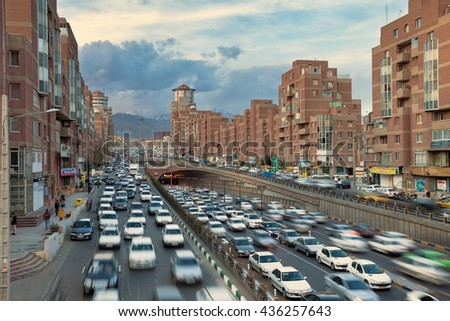 TEHRAN, IRAN - FEBRUARY 19, 2016: Cars Passing Through Tohid Tunnel with Milad Tower and Alborz Mountains in Background. Tohid Tunnel is the third longest urban tunnel in Middle East. - stock photo