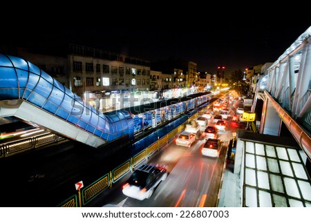 TEHRAN, IRAN - OCTOBER 6: Transport traffic with lights of cars on the busy street of night urban city on October 6, 2014. With a population of 8.3 million, Tehran is the largest city in Western Asia - stock photo