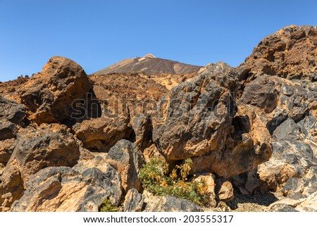 Teide volcano behind volcanic rocks in Tenerife. - stock photo