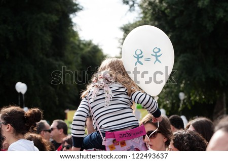TEL AVIV, ISRAEL - DECEMBER 7: A child holds a balloon with a message of equality during the annual human rights march in Tel Aviv, Israel, December 7, 2012. - stock photo