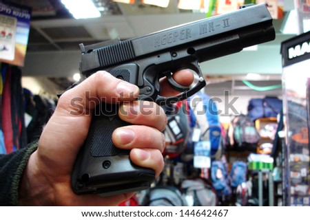 TEL AVIV - MAR 28: Man holds a gun on Mar 28 2007.The United States has 90 guns for every 100 citizens, making it the most heavily armed society in the world - stock photo