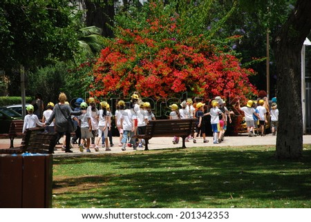 Tel Aviv, May 25, 2014. Schoolchildren group walking in a park together with their educators. - stock photo