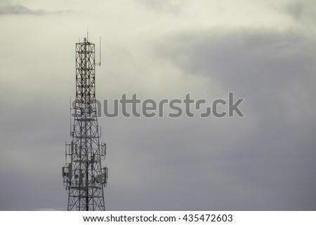 Telecommunication Radio Antenna and Satellite Tower in evening sky. - stock photo