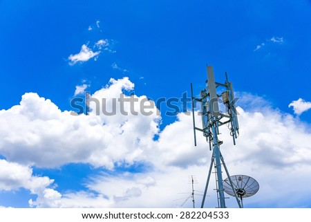 telecommunication tower and satellite dish under cloudy blue sky - stock photo