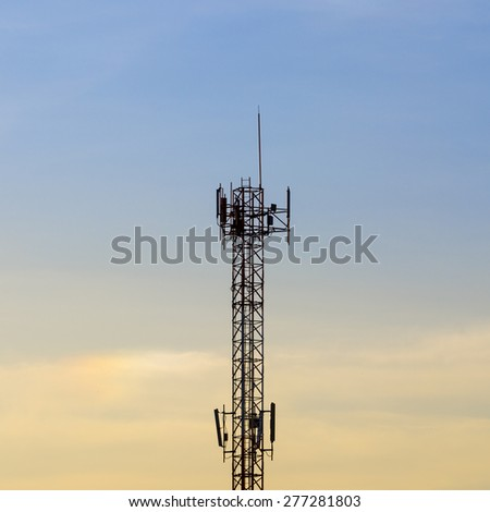 Telecommunication tower in sunset sky background. - stock photo