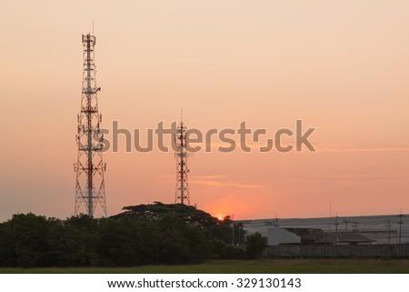 Telecommunication tower sunrise time - stock photo