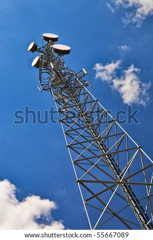 Telecommunication tower with antennas over blue sky. - stock photo