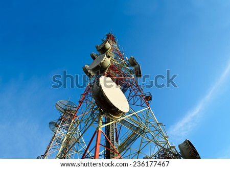 telecommunication towers with antennas against blue sky - stock photo