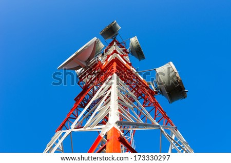 Telecommunications tower, painted white and red in a day of clear blue sky. - stock photo