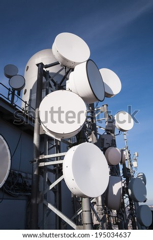 Telecommunications tower with many satellite dish in the city - stock photo