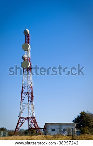 Telecommunications tower with parabolic antennas over a blue sky - stock photo