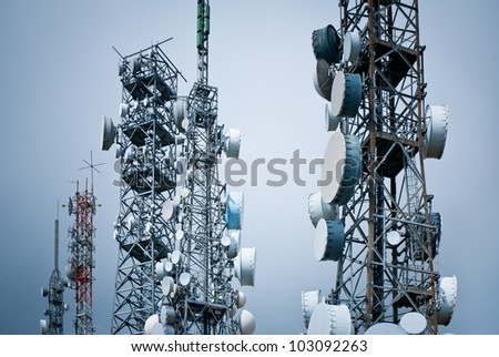 telecommunications towers against a unreal sky - stock photo
