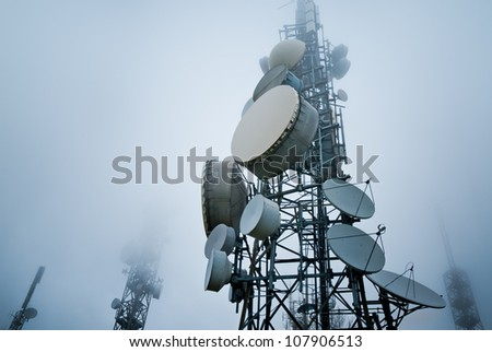 telecommunications towers into the clouds - stock photo