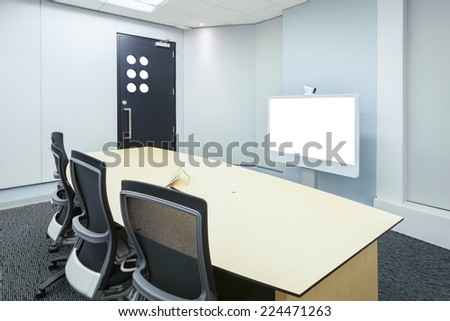 teleconferencing, video conference and telepresence business meeting room with white blank display screen - stock photo