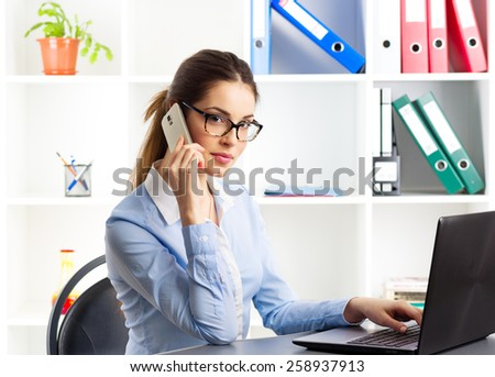 Telemarketing woman. Pretty female consultant talking on phone sitting in front of laptop computer.  - stock photo