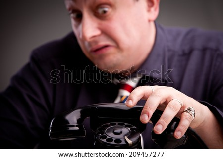 Telephone rings and the clerk is afraid of taking the call - stock photo