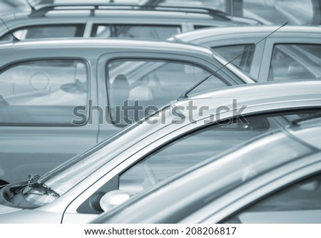 Telephoto image of cars parked in car park (blue toned) - stock photo