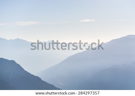 Telephoto view of distant blue toned mountain range at sunrise with clear sky and soft light. - stock photo