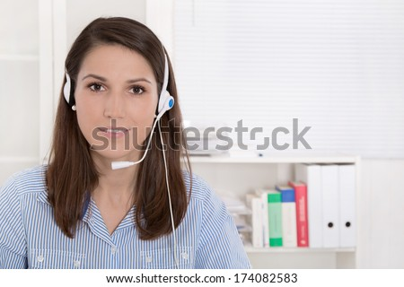 Telesales or helpdesk - helpful woman with headset smiling at camera - stock photo