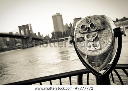 telescope before Skyline of New York City with Brooklyn Bridge, East River - vintage monochrome - stock photo