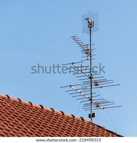 television antenna  on roof with blue sky - stock photo