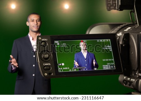 Television presenter recording in a green screen studio, seen through the LCD display of a digital TV camera. Selective focus on the viewfinder. - stock photo
