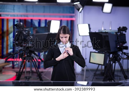 Television presenter recording in news studio.Female journalist anchor presenting report live in front of the audience.News camera,light equipment behind the scenes.Wireless microphone - stock photo