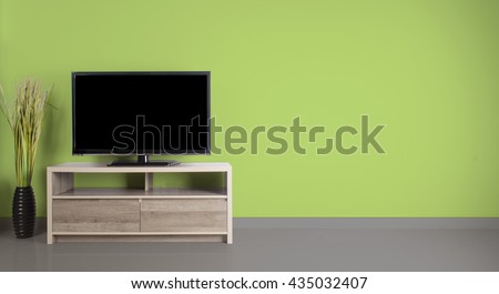 Television put on wood table, background Green wall. - stock photo