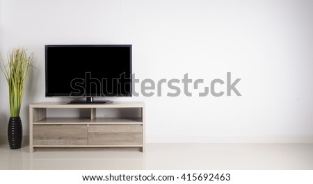 Television put on wood table, background white wall. - stock photo
