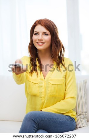 television, relax, home and happiness concept - smiling young girl sitting on couch with tv remote control at home - stock photo