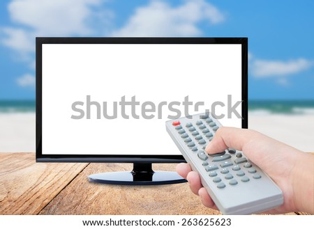 Television remote control watching tv , Sea blur background - stock photo