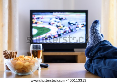 Television, TV watching (formula one race) in living room with feet on table - stock photo - stock photo