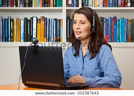 Teleworking woman with laptop, webcam and headphones telephoning visually with a colleague via the internet - stock photo