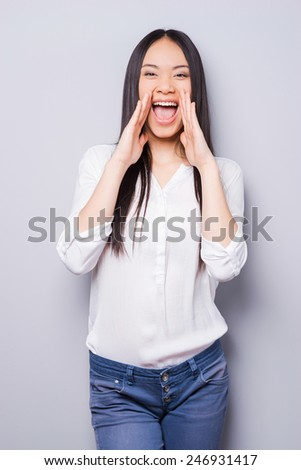 Telling the great news. Attractive young Asian woman shouting and holding hand near mouth while standing against grey background - stock photo
