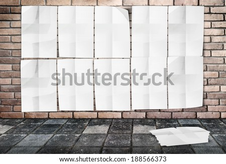 Template- Wall of Crumpled Posters on brick wall & footpath ground - stock photo